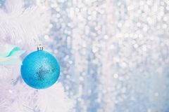 Blue Christmas toy hanging on a white spruce with snow. royalty free stock photo