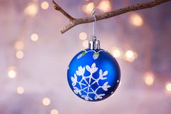 Blue Christmas tree ball with snow flake ornament hanging on branch. Shining garland golden lights. Pastel purple background. Magical atmosphere. Copy space stock photo