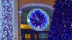 Blue Christmas tree in city with twinkling lights garlands and clock. Closeup stock footage