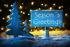 Blue Christmas Tree, Text Seasons Greetings. Sign With English Text Seasons Greetings. Blue Christmas Tree With Snow And Magic Glowing Lights In Backround. Card Stock Image