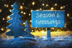 Blue Christmas Tree, Text Seasons Greetings, Snowflakes. Sign With English Text Seasons Greetings. Blue Christmas Tree With Snow And Magic Glowing Lights In Royalty Free Stock Photography
