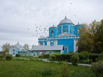 The blue church in the autumn, in cloudy weather. ACHINSK, RF - September: The main temple of Achinsk. The Orthodox Church of the Icon of the Mother of God of Royalty Free Stock Photo