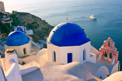 Blue Church Domes, Greece. The domes of a traditional greek church high on the cliffs in Oia, Santorini, with a large yatch going past on the sea below Stock Photos