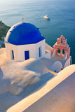 Blue Church Domes, Greece. The domes of a traditional greek church high on the cliffs in Oia, Santorini, with a large yatch going past on the sea below Royalty Free Stock Photo