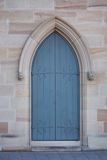 Blue church door set in a sandstone archway. A blue wooden church door set in an archway of an historic sandstone cathedral Royalty Free Stock Photos