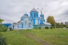 The blue church with outbuildings, in the autumn, in cloudy weather. ACHINSK, RF - September 26, 2013: The main temple of Achinsk. The Orthodox Church of the Stock Photo
