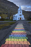 Blue Church and rainbow road in Seydisfjordur Stock Image