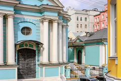 Blue  church with white pillars in  the middle of colorful houses. In Russia Stock Photo