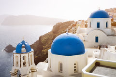 Blue churches of Oia village and sea at Santorini island, Greece. Blue and white churches with beautiful view of the sea and Oia village in Santorini island Royalty Free Stock Image