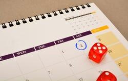 Blue Circle markerade på kalender med röd tärning Royaltyfri Fotografi
