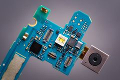 Blue circuit board from smartphone with camera module on a ribbon cable. Blue circuit board from smartphone with camera next to sim card slot royalty free stock photos