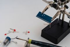 Blue circuit board in soldering helping hands stock photo