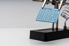 Blue circuit board in soldering helping hands royalty free stock photo