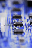 Blue Circuits. Circuit board detail with microchips on blue blurry background Stock Images