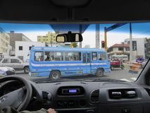 Blue city bus through vehicle windshield. A blue city bus crossing a road junction as seen through windshield of another vehicle in the city of Lima, Peru Royalty Free Stock Photos