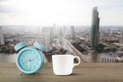 Blue classic alarm clock and hot white coffee cup with steam on vintage wooden desk on blurred city background Royalty Free Stock Photo
