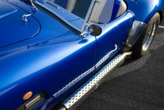 Blue classic American muscle car. Metallic blue classic American muscle car with chrome side exhaust Royalty Free Stock Photos