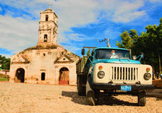 Blue classic American track and destroyed historic church on one of the squares of Trinidad. Where old cars are relic of Cuban revolution and still attracts Royalty Free Stock Photos