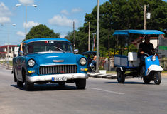 A blue classic car drived on the street Stock Image
