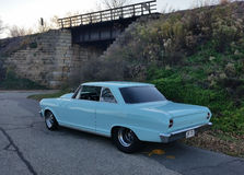 Blue classic car parked by bridge on fall day Stock Photo