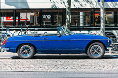 Blue classic car parked on the street. Blue beautiful classic car without the roof parked among the bicycles Stock Image