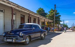 Blue classic car with white roof parked in havana Cuba with street life view Royalty Free Stock Photography