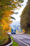 Blue classic modern semi truck on winding autumn road Stock Images