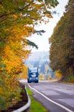 Blue classic modern semi truck on winding autumn road