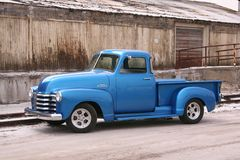 Blue classic pickup with contrasting background. My shiny blue 1953 chevy pickup truck is parked on in front of an old building. The contrast between the shiny Stock Photos