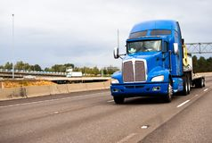 Blue classic powerful big rig semi truck with high cab and flat Royalty Free Stock Photo
