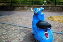 Blue classic scooter or vespa Peugeot Django parked in the street