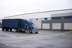Blue classic semi truck with container on warehouse buildings pl Royalty Free Stock Photography