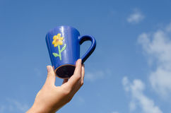 Blue clay cup flower in hand blue sky background. Blue clay tea cup with flower in hand on blue sky background Stock Photos