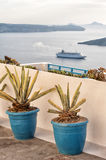 Blue clay pots in Santorini  Greece. Blue clay pots on a balcony with the sea and cruise ship in the background Royalty Free Stock Image