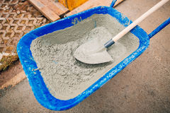 Blue clean new wheelbarrow for cement. Laying the first shovel c Royalty Free Stock Photo