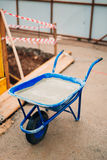 Blue clean new wheelbarrow for cement. Laying the first shovel c Royalty Free Stock Image