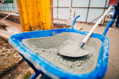 Blue clean new wheelbarrow for cement. Laying the first shovel c Stock Photo
