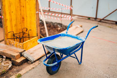 Blue clean new wheelbarrow for cement. Laying the first shovel c Stock Images