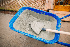 Blue clean new wheelbarrow for cement. Laying the first shovel c Stock Photography