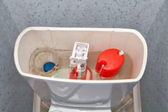 Blue cleaner water soluble tablet falls into toilet flush tank. Royalty Free Stock Photo