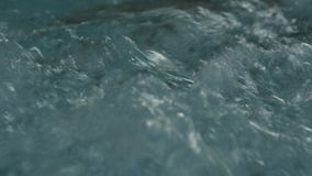 Blue clear rippled water with bubbles in jacuzzi. slow motion