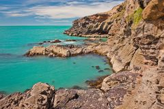 Blue clear water of Bay near Christchurch city in New Zealand. Walking along the rocky cliffs, New Zealand seascape, incredibly beautiful water, day trip from royalty free stock photo