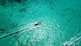 Blue clear water with a fishing boat. Aerial view from the drone. The turquoise color of the water shimmers. You can see the bottom. Brown Asian boat. Thailand royalty free stock photo