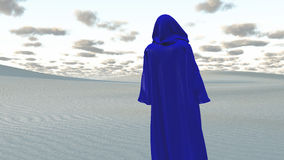 Blue Cloaked Figure in Desert. Blue Cloaked Figure in Empty Desert Royalty Free Stock Photos