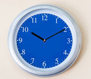 Blue clock. On white wall Royalty Free Stock Images
