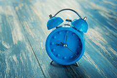Blue clock on antique rustic wood. Background Royalty Free Stock Images