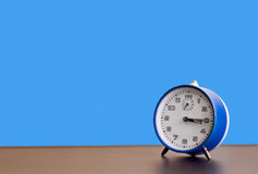 Blue clock. On blue background Royalty Free Stock Images