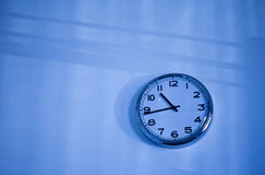 Blue clock on a blue wall Royalty Free Stock Photos