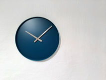 Blue clock on white wall Royalty Free Stock Images