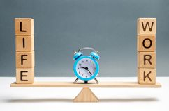 Blue clock between the words life and work on the scales. choice between life and work. The concept of paying attention to the. Life values, promotion at work stock photos